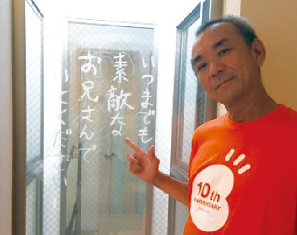 写真:メッセージ(いつまでも素敵なお兄さんでいてください)を指差す日本理化学工業大山氏