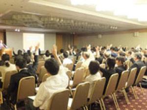 写真:挙手をする聴講者