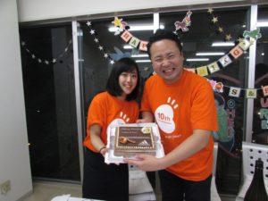 写真:ケーキを持って喜ぶ小川の息子とお嫁さん