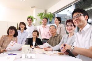 写真:ブライト社員5人と高齢者モニター4人が会議室で微笑んでいる様子