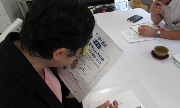 写真:弱視の女性が冊子を目に近づけて読む様子