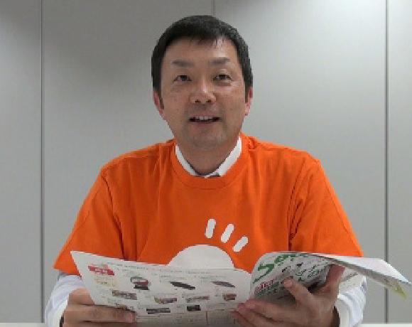 写真:情報誌を手に持ち、語りかけている様子の福利厚生センター佐藤氏
