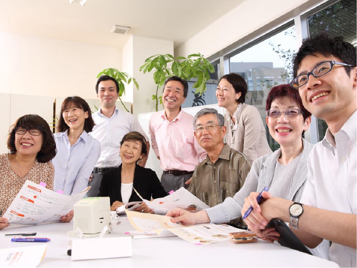 写真:ブライト社員5人と高齢者モニター4人が微笑んでいる様子