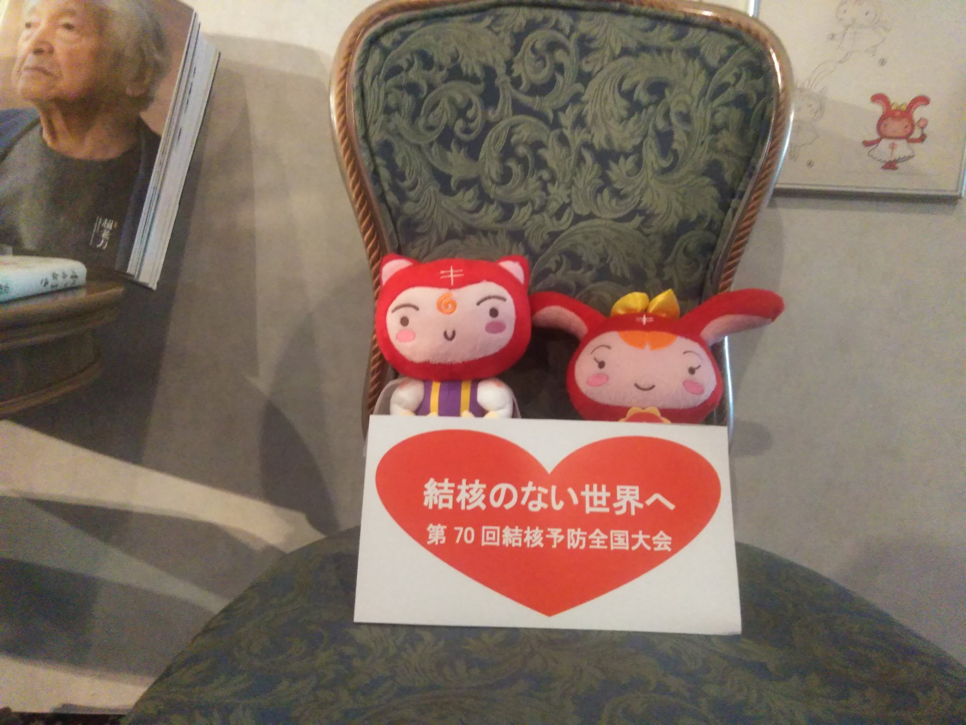 写真です。シールぼうやというキャラクター2体が、椅子の上に座っております