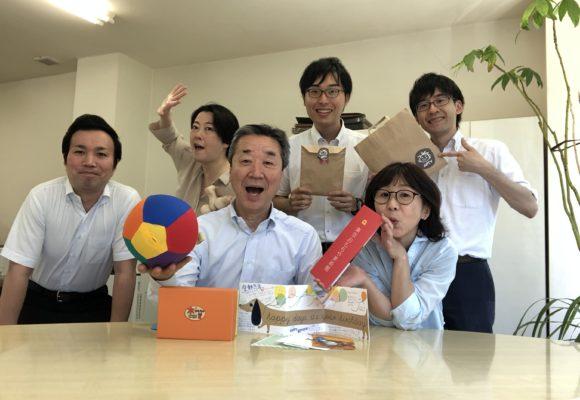 写真:社長とおもちゃを囲んだ集合写真