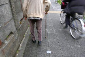 写真:高齢者が杖を付いて歩く様子