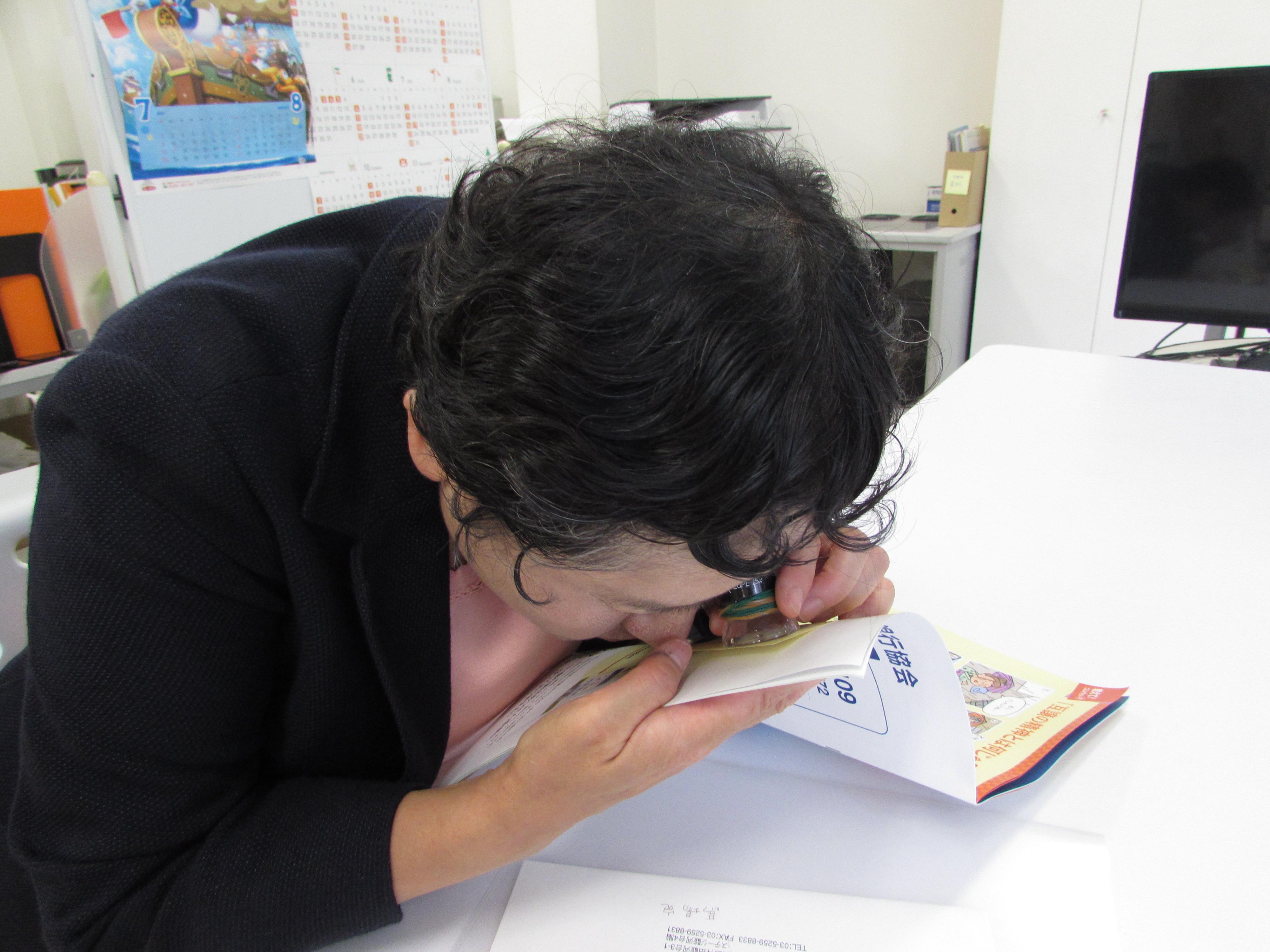 写真:ルーペで冊子を読む女性