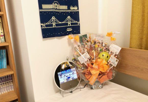 写真:お客さまよりいただいたフォトフレームと手ぬぐい。会社からいただいたお菓子の花束と一緒に