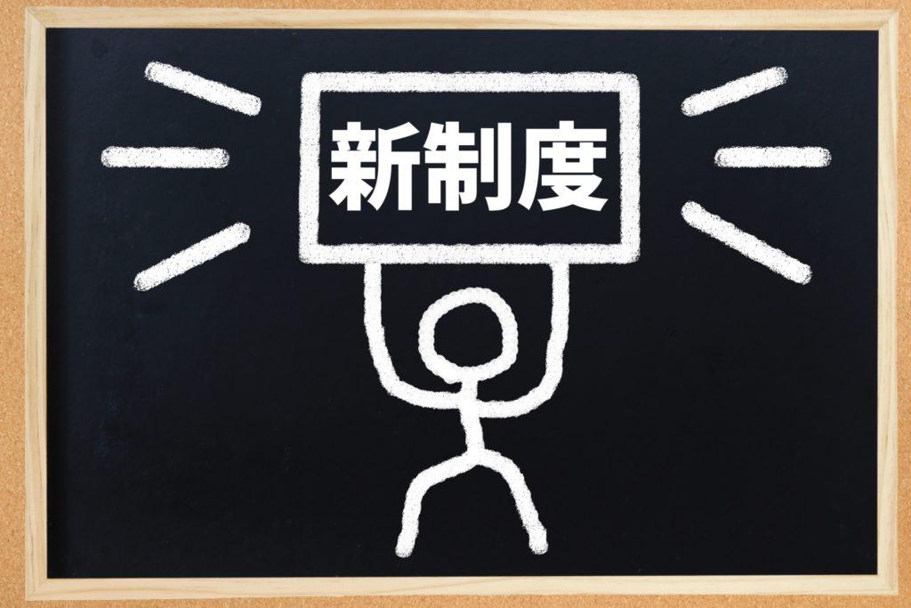 イメージ画像:新制度の看板を掲げた人