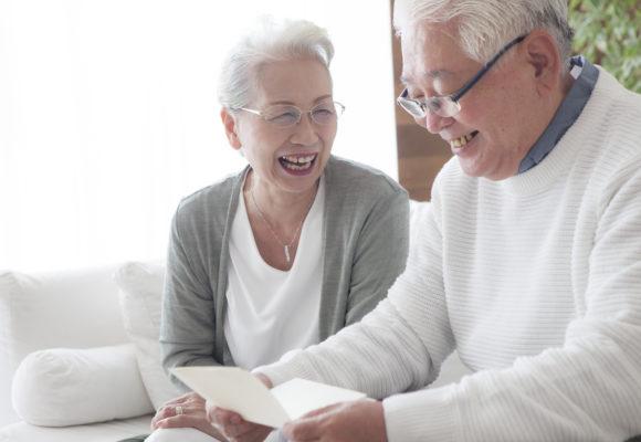 写真:笑顔でパンフレットを読んでいる老夫婦