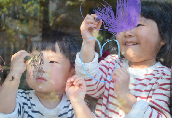 写真:子ども2人が窓に、キットパスでお絵かき
