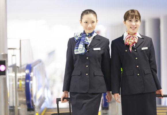 イメージ画像:空港でスーツケースを引くキャビンアテンド2名