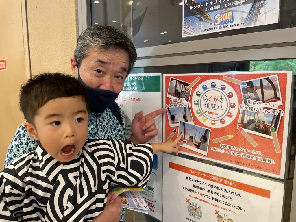 写真:チケット売り場でポスターを指差す孫とじいじ