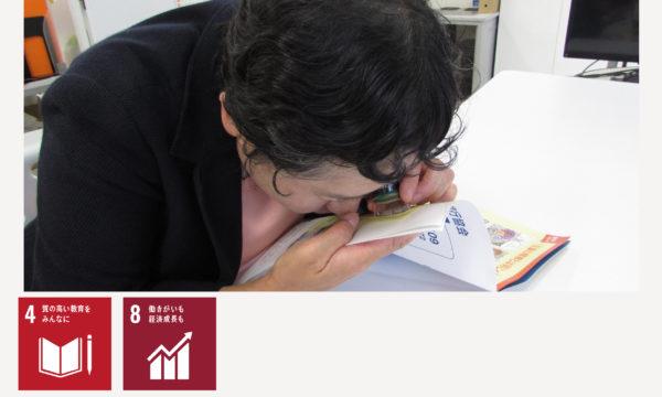 画像:ルーペで冊子を読む視覚障害者の女性